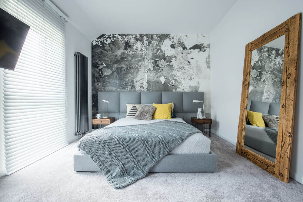 A grey bedroom interior with a full length mirror and a grey bed with white bedsheets.