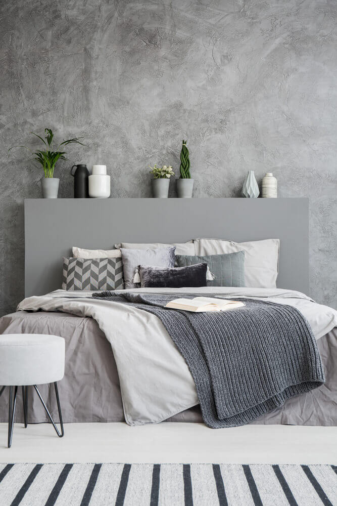 A comfortable bed with linen, pillows, a blanket and an open book on it in a grey style bedroom interior. Green plants and vases as decorations.