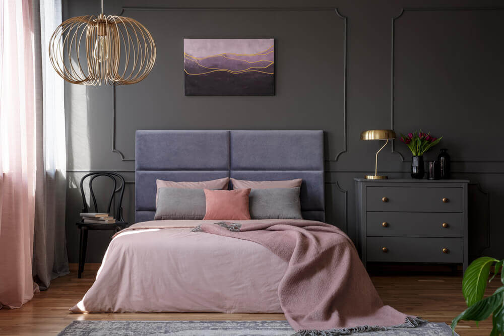 A dark grey bedroom interior with a grey bed and pale pink and coral bed sheets.