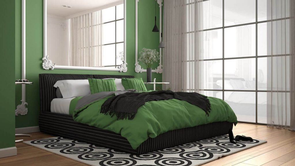 Modern green colored bedroom in classic room with wall moldings, parquet, double bed with duvet and pillows, minimalist bedside tables, mirror and decors