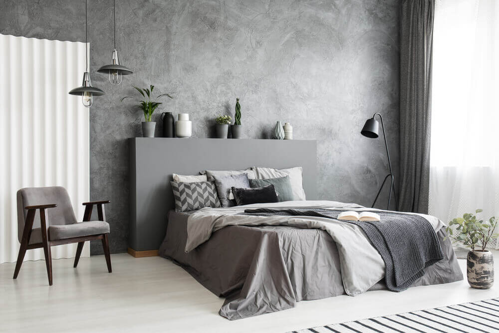 Modern grey bedroom interior with big bed with grey sheets, pillows and linen.