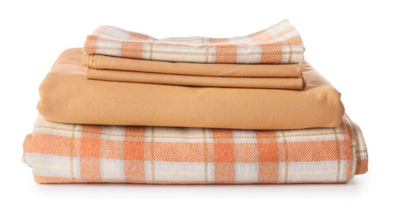A stack of clean coral patterned flannel bed sheets.