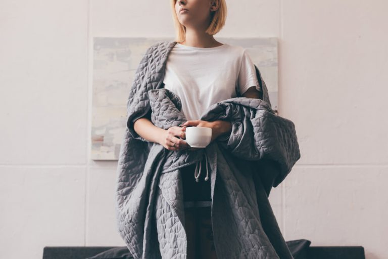 Woman wrapped in an anchor blanket which may help with insomnia and anxiety