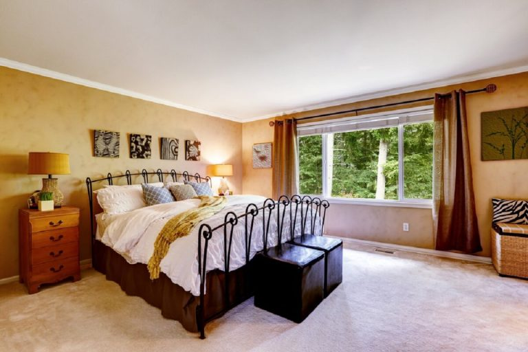 Luxury bedroom in peach color, metal bed frame, bed skirt, two leather benches at the end of bed.