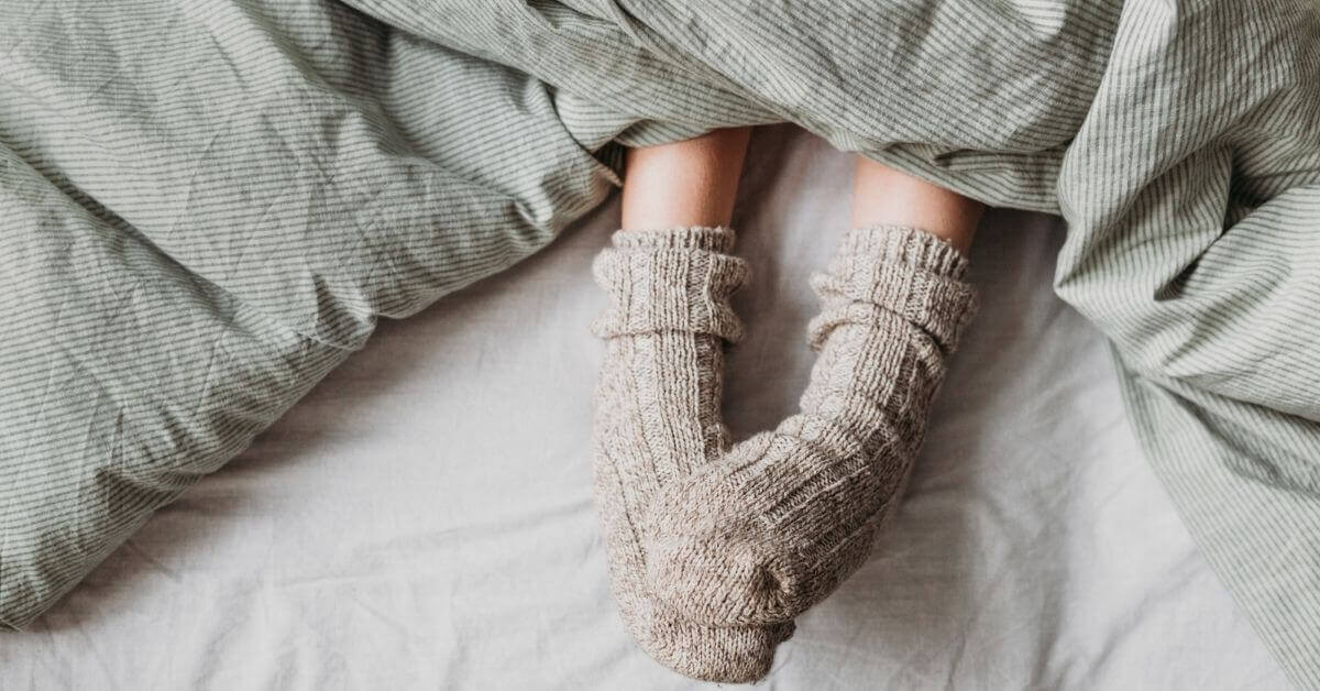 Sleeping with thick woolly socks on under bed covers