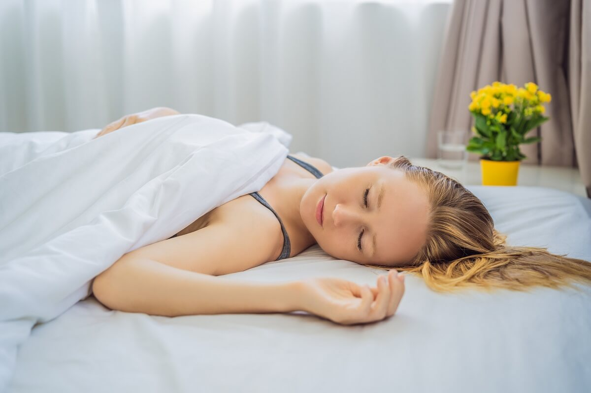 Young female sleeping on her back without a pillow