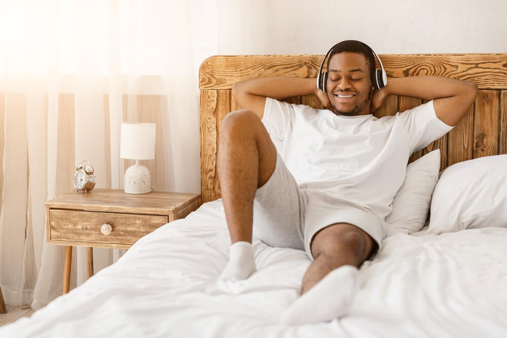 Young man, relaxed in bed, listening to music using headphones